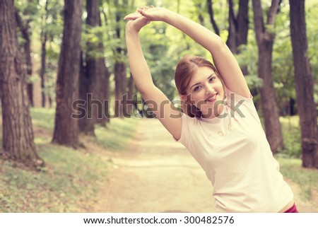 Fitness woman stretching exercises on fresh air. Beautiful sportswoman exercising outdoors in park on summer spring day. Young sporty girl doing pilates.  - stock photo