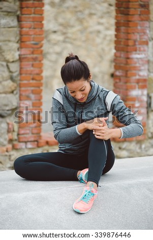 Fitness woman suffering knee injury or kneecap pain after running or working out. - stock photo