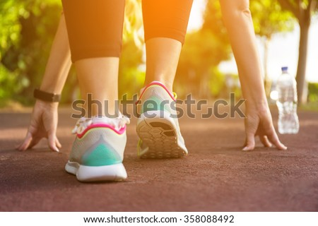 Fitness woman training and jogging in summer park. Ready to start. Healthy lifestyle and sport concept - stock photo