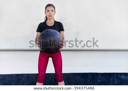 Fitness woman training arms doing biceps curls exercises holding medicine ball in outdoor crossfit gym. Young Asian athlete girl doing upper body strength training workout with heavy weighted balls. - stock photo