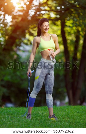 Fitness woman with a skipping rope and a bottle of water outdoors. Fitness training outdoors. Fitness classes outdoors. Attractive fitness woman. Sports and fitness - concept of healthy lifestyle. - stock photo