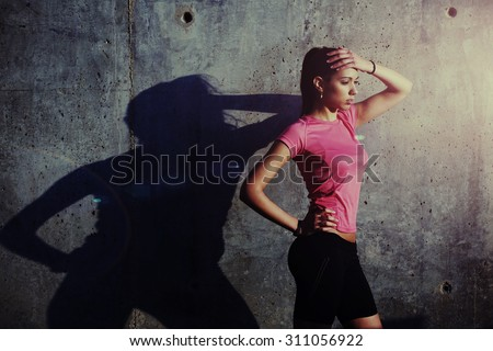 Fitness woman with beautiful figure holding hand above her head while rest after run outdoors, attractive female runner taking break after workout while standing against concrete wall with copy space - stock photo
