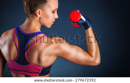 Fitness woman with dumbbells on a dark background. Back view