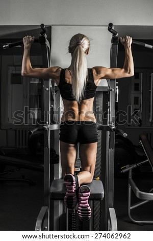 Fitness Woman with smiling face looking at camera. Close-up young adult blond girl with long hair holding simulator for swing press expressed muscles in arms on dark green wall background Back view - stock photo