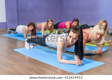 Fitness women practicing the side plank yoga pose during a class in a gym