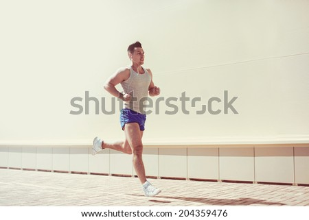 Fitness, workout, sport, lifestyle concept - man running in the city - stock photo