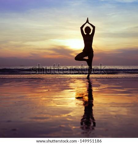 fitness, yoga on the beach - stock photo