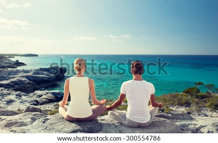 fitness, yoga, people and lifestyle concept - couple meditating on beach from back - stock photo
