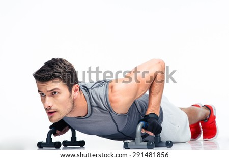 Fitness young man doing push ups isolated on a white background. Looking away