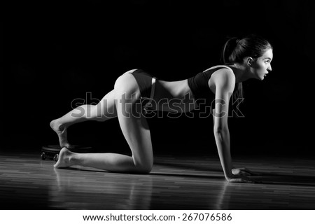 Fitness young sexy girl in the gym doing exercises with abdominals. Sexy young fitness girl pulls up in the gym. Brunette fitness woman in black sport wear with perfect fitness body. - stock photo