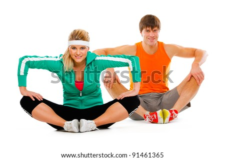 Fitness young woman and man in sportswear doing stretching exercise on floor