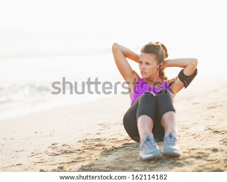 Fitness young woman doing abdominal crunch on beach and looking on copy space - stock photo