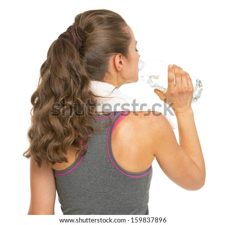 Fitness young woman drinking water . rear view