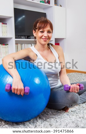 Fitness young woman, exercising with dumbbels and pilates ball at home.