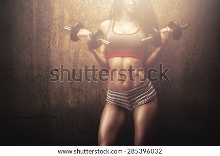 Fitness young woman in hard training building muscles and posing in front of gym wall - stock photo