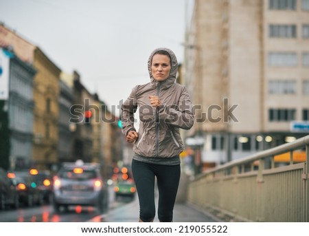 Fitness young woman jogging in rainy city - stock photo
