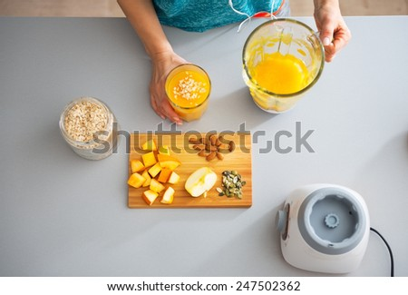 Fitness young woman making pumpkin smoothie - stock photo