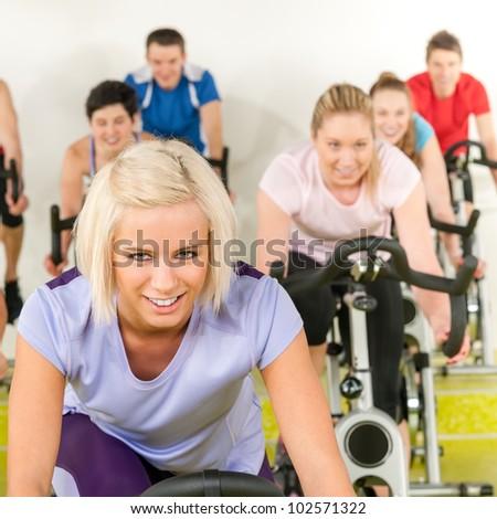 Fitness young woman on gym bike indoor cardio exercise - stock photo