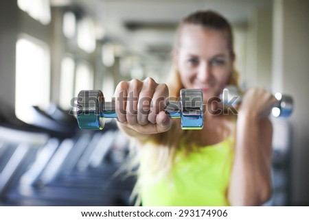 Fitness young woman with barbells on gym background - stock photo