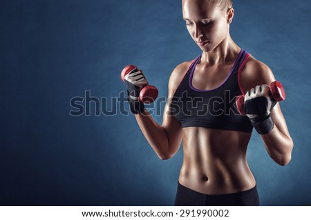 Fitness young woman with dumbbells on a dark background - stock photo