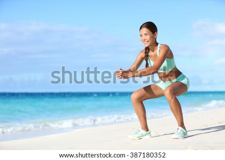 Fitness young woman working out core and glutes with bodyweight workout doing squat exercises on beach. Asian sporty girl squatting legs as part of an active and fit life. - stock photo