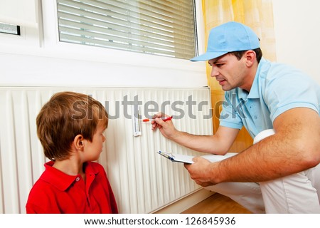 fitter with radiator. save energy. reading the heating - setting. - stock photo
