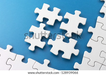 Fitting four puzzle pieces.Concept image of building. - stock photo