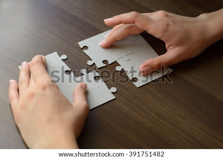 fitting of jigsaw puzzles on wooden table. Macro with blur and soft focus - stock photo