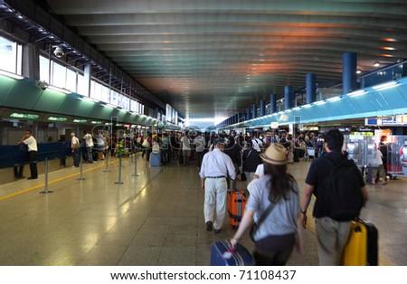 FIUMICINO, ITALY - AUGUST 6: Crowd people in passageway for registration inside Leonardo da Vinci-Fiumicino Airport - largest airport in Italy on August 6, 2010 in Fiumicino near Rome, Italy. - stock photo