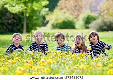 Five adorable kids, dressed in striped shirts, hugging and smiling, sitting on the grass in a dandelion field. Friendship concept - stock photo