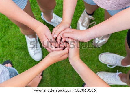 Five arms with hands of young girls entwined above green grass - stock photo