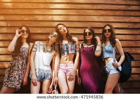 five beautiful girls pose in front of a wooden wall