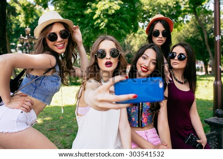 five beautiful young girls make selfie in the park - stock photo
