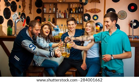 Five best friends clink glasses in the bar and laughing. horizontal photo - stock photo