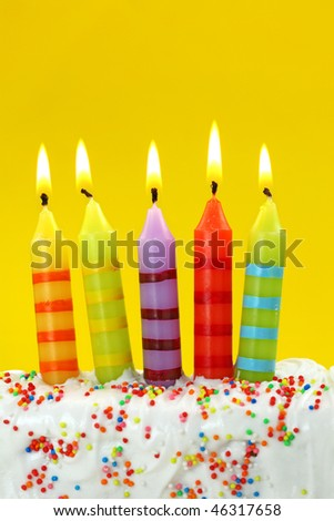 Five birthday candles on yellow background