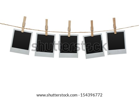 Five blank photos hanging on the clothesline isolated on white background with clipping path for the inside of the frames - stock photo