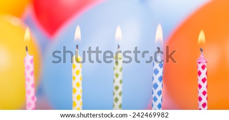 Five burning birthday candles with balloons in background
