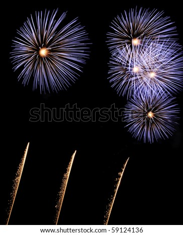 Five bursts of blue and white fireworks with white-hot cores above three glittery rocket trails - stock photo