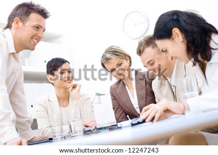 Five business colleagues sitting around table and working together, smiling.