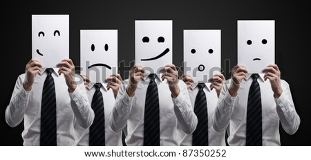 Five business men holding a card with emotional face. On a black background - stock photo