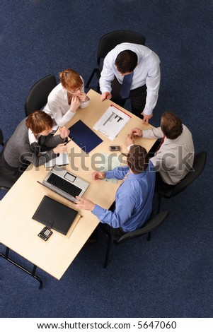 five business people meeting - boss speech,Businesspeople gathered around a table for a meeting, brainstorming. Aerial shot taken from directly above the table. - stock photo