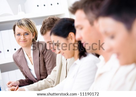 Five business people sitting in a row, making notes. The aftermost businesswoman leaning out of line and looking at camera, smiling.