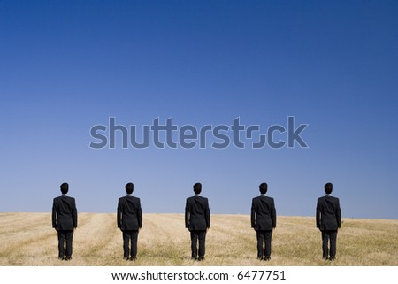 Five businessman in the field trying to find a ecological solution - stock photo