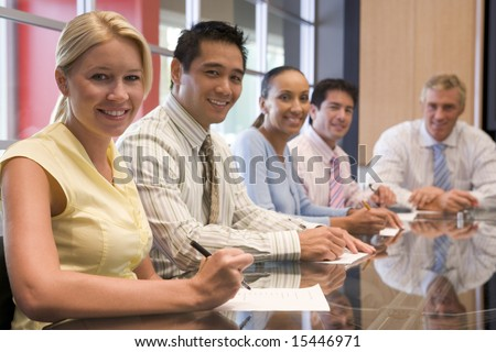 Five businesspeople in boardroom smiling - stock photo