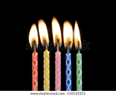 Five candles on black background