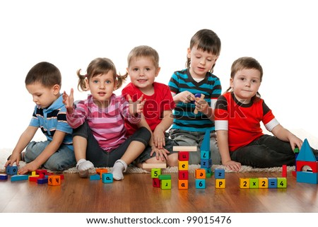 Five children are playing on the floor together - stock photo