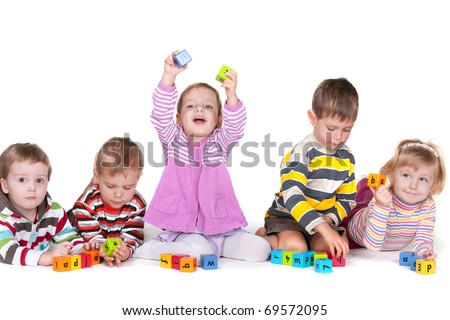Five children are playing vivid blocks with letters; isolated on the white background - stock photo