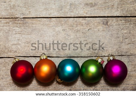 five christmas balls on wooden background, in the colours red, orange, blue, green and pink - stock photo