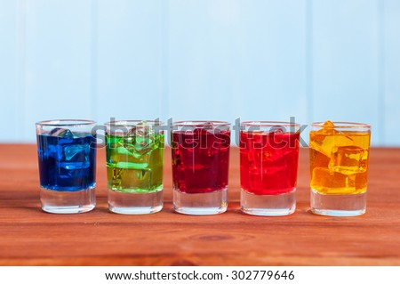 Five cocktails or liqueur on the wooden background. - stock photo