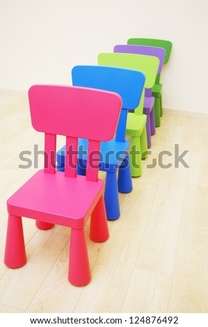 Five colorful chairs in line in Montessori Kindergarten Preschool Classroom